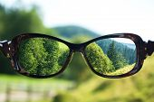 Creative Concept About Poor Vision. Landscape Focused In Glasses Lenses Over The Photo Blurred poster