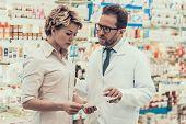 Pharmacist Counseling Female Customer In Drugstore. Pharmacist Wearing White Coat And Glasses Holdin poster