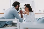 Young Couple Drinking Coffee Together At Home. Handsome Man Sitting At Table Next To Beautiful Woman poster