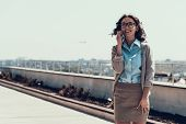 Young Smiling Woman Talking On Cellphone Outdoor. Portrait Of Beautiful Business Woman Wearing Glass poster