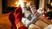 Closeup Photo Of Female Feet In Warm Woolen Socks Warming By The Fireside At House poster