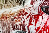 Red Compact Suv Car With Sport And Modern Design Washing With Soap. Car Covered With White Foam. Car poster