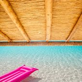 Cane sunroof with tropical perfect beach and  pink float  [photo-illustration]