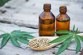 Hemp Leaves On Wooden Background, Seeds, Cannabis Oil Extracts In Jars poster