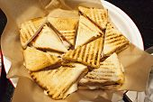 Top View, Triangle Shaped, Toasted White Bread Club Panini Sandwiches With Ham, Cheese And Tomato poster