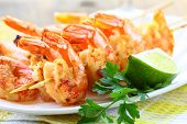 stock photo of crustacean  - ready to eat grilled shrimp with lime and parsley - JPG