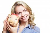 Happy blonde woman smiling with piggy bank near her cheek
