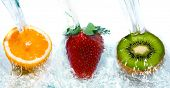Fresh fruit jumping into water with a splash