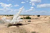 stock photo of landmines  - Large explosion near the car with soldiers in the desert - JPG