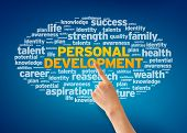 image of self assessment  - Hand pointing at a Personal Development Word Cloud on blue background - JPG