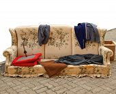 foto of hobo  - Old sofa with clothes used by poor homeless hobo - JPG