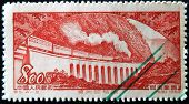 A stamp shows passenger train with steam locomotive on the railroad viaduct Chungking-Chengtu
