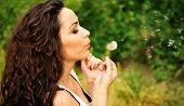 Portrait of a young beautiful woman with a dandelion