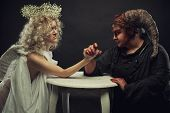stock photo of wrestling  - Demon and angel have competition at arm wrestling on a table - JPG