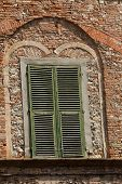 old wall and ancient italian window with green shutters