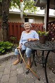 Elderly Woman Sitting at Table in Back yard