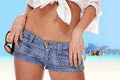 picture of swimsuit model  - Close up of a Young fashion woman in jeans shorts posing on the beach - JPG