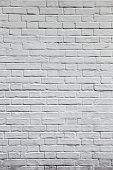 Grungy textured white vertical stone and brick paint architecture wall inside old neglected and deserted interior, masonry and carpentry brickwork concept