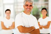 smiling middle aged sporty man with arms folded in front of family at home