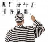 stock photo of prison uniform  - Convict prisoner jailbird is counting days in jail - JPG