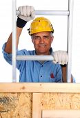 Closeup of  a construction worker climbing a ladder isolated over white. The man wearing a work shirt, gloves and a hard hat is partially hidden behind a wood framed wall. Vertical Format.