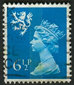UK-CIRCA 1976: A stamp printed in UK shows image of Elizabeth II is the constitutional monarch of 16