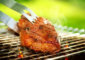 Flames Grilling a Steak on the BBQ. Grilled Meat Preparing. Grill Beef Steak Barbeque.  Barbecue outdoor. Barbecued Fillet