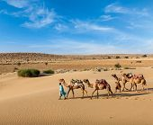 Rajasthan travel background - two Indian cameleers (camel drivers) with camels in dunes of Thar dese