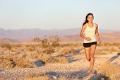 Woman runner running cross country trail run. Female jogger training outside on path outdoors at sum