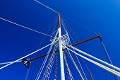 Sailing boat mast with pirate flag against a blue sky