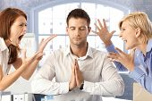 stock photo of yell  - Meditating closed eye businessman in office with arguing colleagues shouting and fighting - JPG