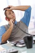 Troubled businessman at desk concentrating on landline phone call, holding mobile phone, looking up.