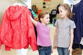 Two girls try on clothes in a modern store childrens clothes, focus on left girl