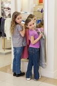 Two cute girls near a mirror try on clothes in a store childrens clothes, focus on left girl