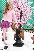 Girl next to artificial cherry blossom touches big chess pieces on big chessboard in park. Focus on
