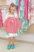 Little girl stands holding hanger with pink jacket