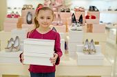 stock photo of department store  - Little girl stands and holds two shoe boxes in shoe store - JPG