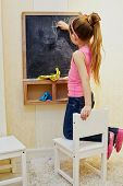 Little girl girl writes with chalk on blackboard, kneeling on chair