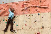 pic of climbing wall  - Young climber rises to the climbing wall - JPG