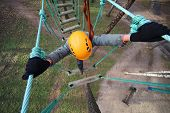 Boy climber walks on the rope bridge, the view from above