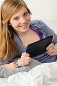 Happy young girl using digital tablet for studying