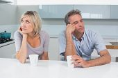 Displeased couple sitting with coffee cups in the kitchen at home