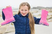 Portrait of a cute smiling young girl holding her wellington boots at the beach