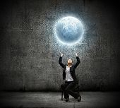 image of businesswoman holding moon in hands above head