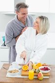 Man with a happy woman as she cuts fruits in the kitchen at home