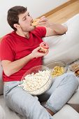 pic of couch potato  - Lazy guy on a couch with heap of food - JPG