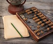 stock photo of kerosene lamp  - Old abacus the paper with a pencil next to a kerosene lamp on a wooden table - JPG