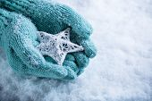 Female hands in light teal knitted mittens with entwined white star on a white snow background. Wint