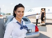 Portrait of beautiful stewardess standing against limousine and private jet at airport terminal