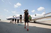 Rear view of woman walking towards private jet while pilot and stewardesses standing at airport terminal